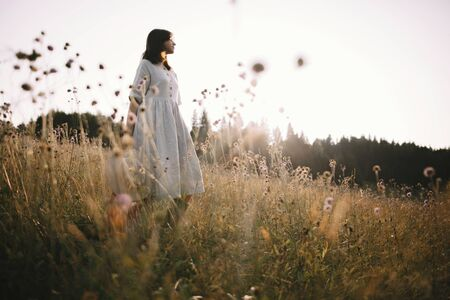 Stylish girl in rustic dress standing among wildflowers and herbs in sunny meadow  in mountains. Boho woman relaxing in countryside at sunset, simple life. Atmospheric image. Space text