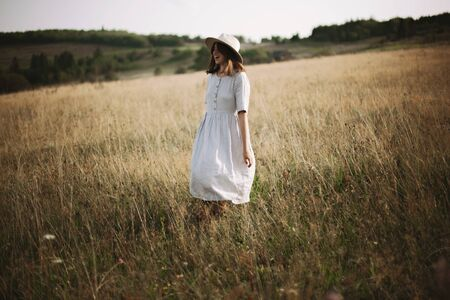 Stylish girl in linen dress walking among herbs and wildflowers in meadow. Boho woman relaxing in countryside, simple slow life style. Atmospheric image. Space text Фото со стока