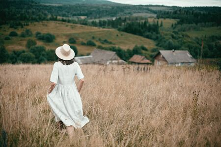 Stylish girl in linen dress and hat walking among herbs and wildflowers in field. Boho woman relaxing in countryside, simple slow life, amish style. Space for text. Atmospheric image