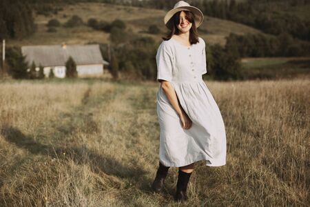 Stylish girl in linen dress and hat running and smiling in sunny field grass at village  in mountains. Boho woman relaxing in countryside, simple rustic life. Atmospheric image. Space text Фото со стока