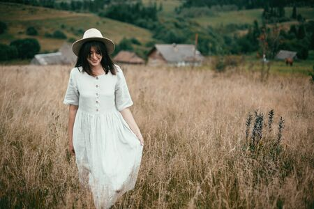 Stylish girl in linen dress and hat walking among herbs and wildflowers in field. Boho woman smiling and relaxing in countryside, simple slow life style. Space for text. Atmospheric image