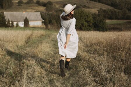 Stylish girl in linen dress and hat running and smiling in sunny field grass at village  in mountains. Boho woman relaxing in countryside, simple rustic life. Atmospheric image. Space text Banco de Imagens