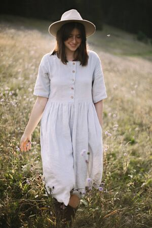 Stylish girl in rustic dress and hat walking among wildflowers and herbs in sunny meadow in mountains. Boho woman relaxing in countryside at sunset, simple life. Atmospheric image Banco de Imagens