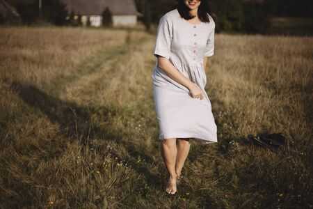 Stylish girl in linen dress and hat running barefoot in grass in sunny field at village. Boho woman relaxing in countryside, simple rustic life. Atmospheric image. Space text
