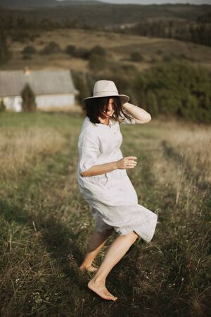 Stylish girl in linen dress running barefoot among herbs and wildflowers in sunny field in mountains. Boho woman relaxing in countryside, simple rustic life. Atmospheric image. Space text Banco de Imagens