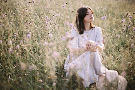 Stylish girl in rustic dress sitting among wildflowers and herbs in sunny meadow in mountains. Boho woman relaxing in countryside at sunset, simple life. Atmospheric image. Space text