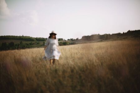 Herbs and wildflowers in sunny meadow in mountains and blurred image of girl in linen dress walking. Boho woman relaxing in countryside, simple rustic life style. Atmospheric image Фото со стока