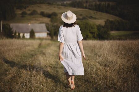 Stylish girl in linen dress and hat walking barefoot in grass in sunny field at village. Boho woman relaxing in countryside, simple rustic life. Atmospheric image. Space text