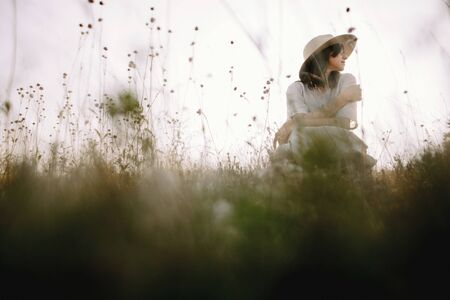 Stylish girl in rustic dress and hat sitting among wildflowers and herbs in sunny meadow  in mountains. Boho woman relaxing in countryside, simple life. Atmospheric image. Space text Фото со стока