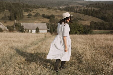 Stylish girl in linen dress and hat walking in sunny field grass at village  in mountains. Boho woman relaxing in countryside, simple rustic life. Atmospheric image. Space text Stok Fotoğraf - 124864640