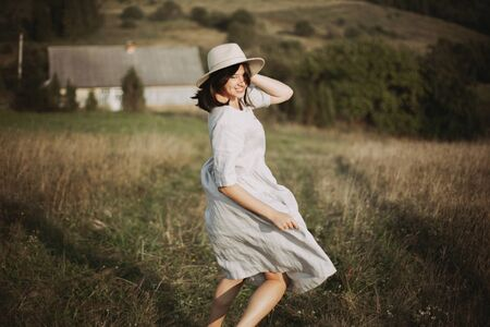 Stylish girl in linen dress running barefoot among herbs and wildflowers in sunny field in mountains. Boho woman relaxing in countryside, simple rustic life. Atmospheric image. Space text Stock Photo