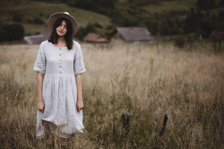 Herbs and wildflowers in field blurred image of stylish girl in linen dress and hat posing. Boho woman relaxing in countryside, simple slow life style. Space for text. Atmospheric image