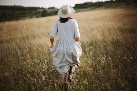 Stylish girl in linen dress running among herbs and wildflowers in sunny meadow in mountains. Boho woman relaxing in countryside, simple rustic life style. Atmospheric image. Space text
