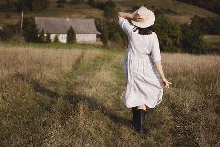 Stylish girl in linen dress and hat walking in sunny field grass at village  in mountains. Boho woman relaxing in countryside, simple rustic life. Atmospheric image. Space text