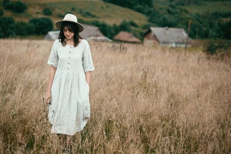 Stylish girl in linen dress and hat walking among herbs and wildflowers in field. Boho woman enjoying day in countryside, simple slow life style. Space for text. Atmospheric image 版權商用圖片