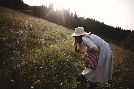 Stylish girl in rustic dress and hat taking photo of wildflowers  in sunny meadow in mountains. Boho woman relaxing in countryside at sunset, simple life. Atmospheric image Фото со стока
