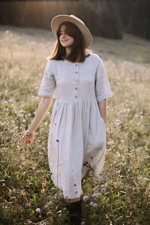 Stylish girl in rustic dress and hat walking among wildflowers in sunny meadow in mountains. Boho woman relaxing in countryside flowers at sunset, simple life. Atmospheric image. Space text Фото со стока
