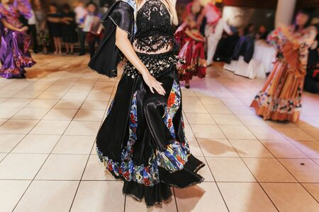 Beautiful gypsy girls dancing in traditional black floral dress at wedding reception in restaurant. Woman performing romany dance and folk songs in national clothing. Roma gypsy festival Stock Photo