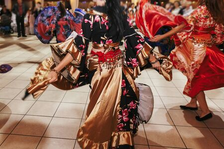 Beautiful gypsy girls dancing in traditional gold floral dress at wedding reception in restaurant. Woman performing romany dance and folk songs in national clothing. Roma gypsy festival Stock Photo