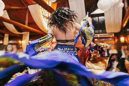 Beautiful gypsy girls dancing in traditional blue floral dress at wedding reception in restaurant. Woman performing romany dance and folk songs in national clothing. Roma gypsy festival