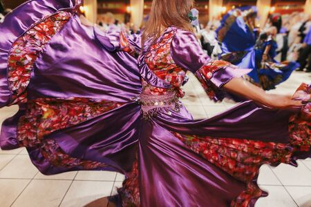 Beautiful gypsy girls dancing in traditional purple floral dress at wedding reception in restaurant. Woman performing romany dance and folk songs in national clothing. Roma gypsy festival