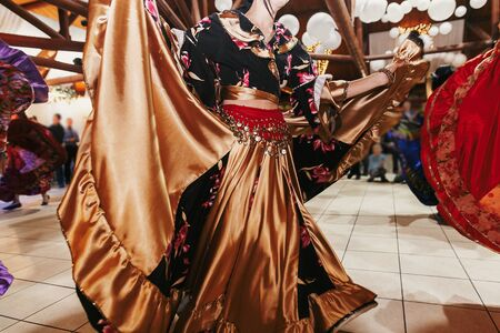 Gypsy dance festival, Woman performing romany dance and folk songs in national clothing. Beautiful roma gypsy girls dancing in traditional floral dress at wedding reception in restaurant