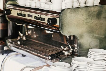 Professional coffee machine in cafe. Big steel and white coffee machine and ceramic cups and plates on table in cafe or wedding reception. Luxury catering
