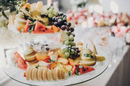 Delicious fruits appetizers, desserts on stand, modern sweet table at wedding or baby shower. Luxury catering concept. Fruit bar at wedding reception, melon,watermelon,grapes,pear slices Stock Photo