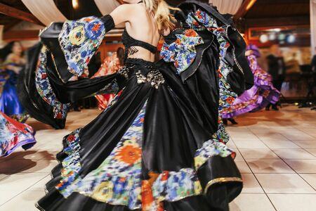 Beautiful gypsy girls dancing in traditional black floral dress at wedding reception in restaurant. Woman performing romany dance and folk songs in national clothing. Roma gypsy festival 写真素材