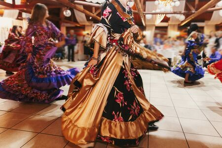 Beautiful gypsy girls dancing in traditional colorful clothing. Roma gypsy festival. Woman performing romany dance and singing folk songs in national dresses at wedding reception 写真素材