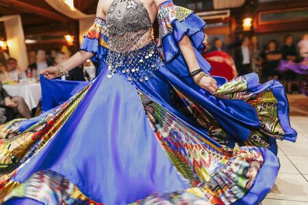 Beautiful gypsy girls dancing in traditional colorful clothing. Roma gypsy festival. Woman performing romany dance and singing folk songs in national dresses at wedding reception Stock Photo