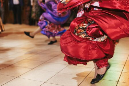 Beautiful gypsy girls dancing in traditional red floral dress at wedding reception in restaurant. Woman performing romany dance and folk songs in national clothing. Roma gypsy festival