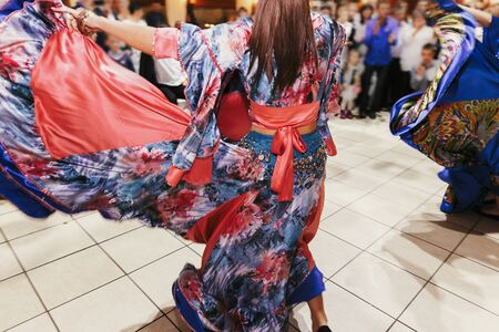 Beautiful gypsy girls dancing in traditional blue floral dress at wedding reception in restaurant. Woman performing romany dance and folk songs in national clothing. Roma gypsy festival 写真素材