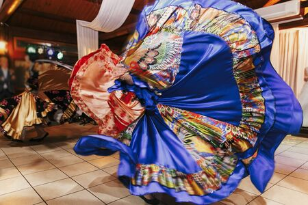 Beautiful gypsy girls dancing in traditional blue floral dress at wedding reception in restaurant. Woman performing romany dance and folk songs in national clothing. Roma gypsy festival Stock Photo