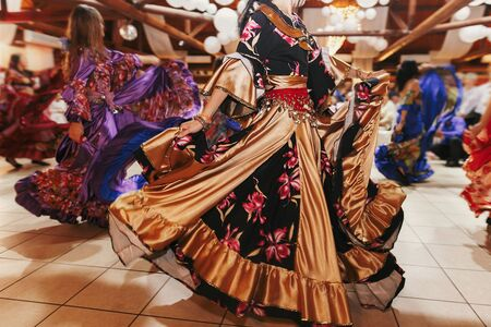 Beautiful gypsy girls dancing in traditional gold floral dress at wedding reception in restaurant. Woman performing romany dance and folk songs in national clothing. Roma gypsy festival 写真素材