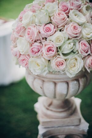 Elegant wedding bouquet on column, stylish decor of wedding aisle outdoors. Pink and white roses arrangement at wedding reception in botanical garden in Stresa