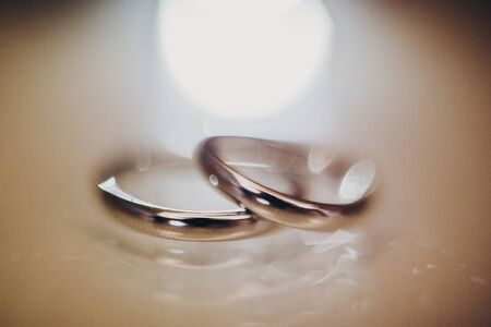 Stylish silver wedding rings on table, macro blurred image with bokeh lights. Wedding jewelry for bride and groom. Marriage and divorce concept. Black and white Stock Photo