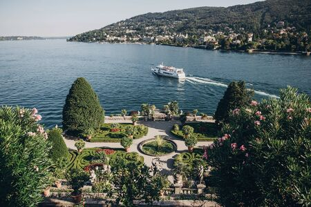Beautiful view of stone landmarks and green terrace with flowers at  Lago Maggiore with ships and boats, exploring  Borromean Islands, Italy. Exploring old architecture monuments in Stresa 写真素材