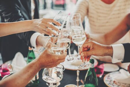 夜の屋外での結婚披露宴でシャンパングラスで乾杯する手。家族や友人がメガネを鳴らし、おいしいごちそうのお祝いでアルコールで応援。クリスマスパーティー