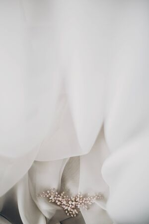 Stylish tender pearl hairpin on soft white tulle in morning light in hotel room. Bridal accessories for the wedding day. Modern jewelry. Morning preparations Reklamní fotografie