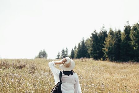 Hipster girl with backpack traveling in sunny mountains, walking in sunny wildflower meadow. Stylish woman in hat exploring and hiking on top of mountain. Wanderlust and travel concept. Space