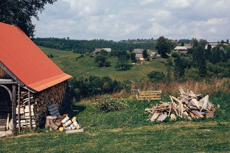 Beautiful view at wooden cabin with firewood, timber pile and green mountain hills with forest and wooden houses in sunny day Carpathian mountains. Exploring Europe. Mountain landscape 스톡 콘텐츠
