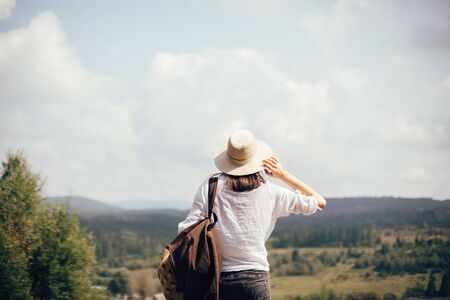 Hipster girl with backpack traveling and standing on top of sunny mountain and looking at sky and woods. Stylish woman in hat enjoying hiking in mountains. Wanderlust and travel