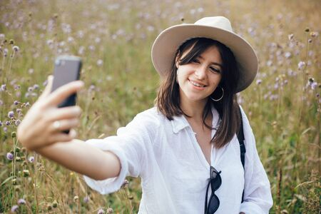 Hipster girl with backpack taking selfie on phone while relaxing in wildflower meadow, traveling in sunny mountains. Stylish woman in hat enjoying hiking on top of mountain. Summer vacation Stock fotó