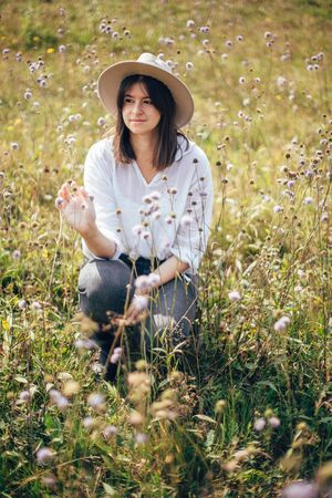 Hipster girl in hat traveling in sunny mountains, relaxing in wildflower meadow. Stylish happy woman enjoying hiking on top of mountain, sitting in herbs. Wanderlust and travel concept