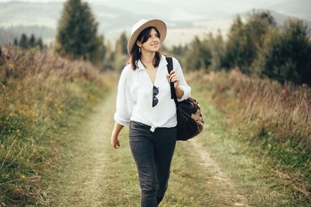 Happy hipster girl with backpack traveling on top of sunny mountain, walking on hills with woods. Stylish woman smiling and  enjoying hiking in mountains. Wanderlust and travel. Stock fotó