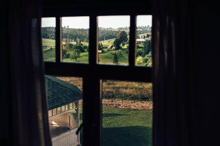 Schöne Aussicht vom Kabinenfenster auf grüne Berghügel mit Wald- und Holzhäusern an sonnigen Tagen. Bäume und Wälder in den Karpaten. Europa erkunden. Berglandschaft