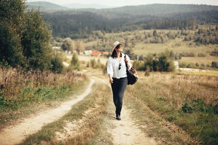 Hipster girl with backpack traveling on top of sunny mountain, walking on hills with woods. Stylish woman smiling enjoying hiking in mountains. Wanderlust and travel. Atmospheric moment