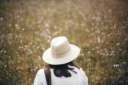 Wanderlust and travel concept. Hipster girl with backpack traveling in sunny mountains, walking in  wildflower meadow. Stylish happy woman in hat exploring and hiking on top of mountain. Stock Photo