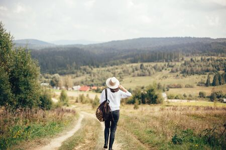 Hipster girl with backpack traveling and walking on top of sunny mountain and looking at sky and woods. Stylish woman in hat enjoying hiking in mountains. Wanderlust and travel